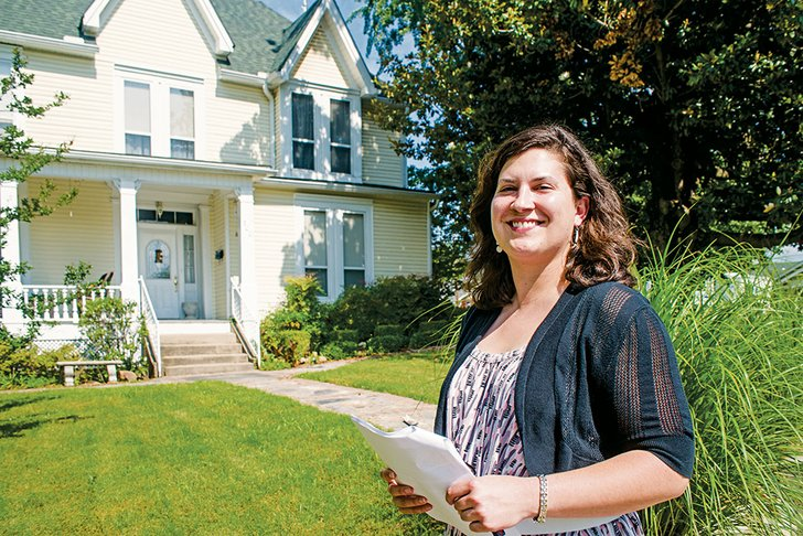Rachel Silva with the Arkansas Historic Preservation Program pauses in front of the G.L. Cunningham House that will be part of the Walks Through History Tour of the Moose Addition Historic District in Morrilton.