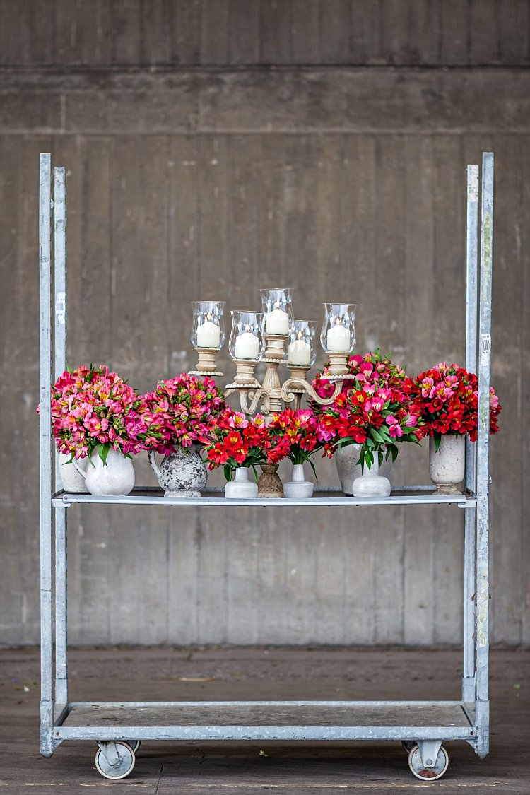 Day 5 of British Flowers Week, featuring a dinner party theme with a collection of ceramic vases flourishing with red and pink alstroemeria and a candelabra with candles ready for light,  designed by Rob Van Helden of Rob Van Helden Floral Designs, presented to you by New Covent Garden Flower Market