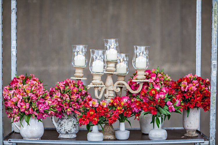 Day 5 of British Flowers Week, featuring a dinner party styled theme with a collection of ceramic vases flourishing with red and pink alstroemeria and a candelabra with candles ready for light, designed by Rob Van Helden of Rob Van Helden Floral Designs, presented to you by New Covent Garden Flower Market