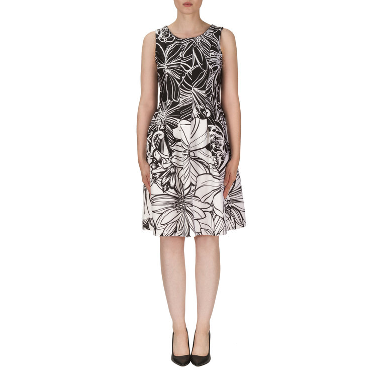 The intricate design of this floral Joseph Ribkoff dress provides a stark contrast against the top and attracts the eye downward, towards the white highlight. The full skirt balances any top heaviness and alludes to a proportional frame.