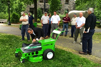 John Vik, grounds manager at Tufts University watches along with his crew as Dan Mabe, president of the American Green Zone Alliance, demonstrates an electric self-propelled mower.