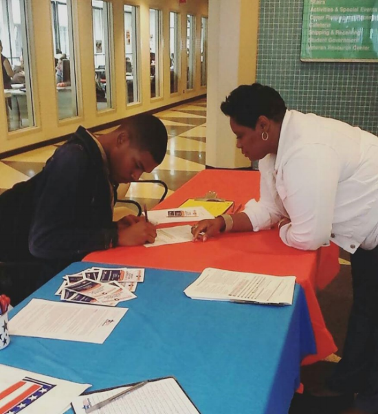 An election staff member signs up a future student poll worker at a recruitment event. Photo by Paulina Mysliwiec.