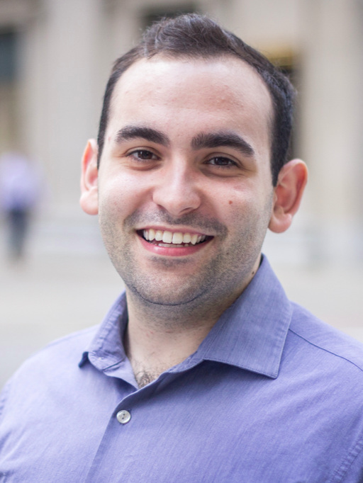 Headshot of Josh Simon Goldman smiling in a blue shirt.