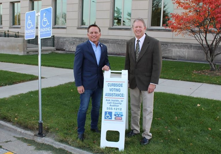 """A lot of voters don't know curbside voting is an option, so having these signs at each voting location are a big help,"" says Secretary Pate (left in photo). Photo from official Facebook page."
