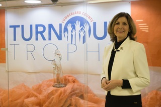 Cumberland County Clerk, Celeste Riley, beside the Turnout Trophy in its display case. Photo courtesy of Cumberland County.