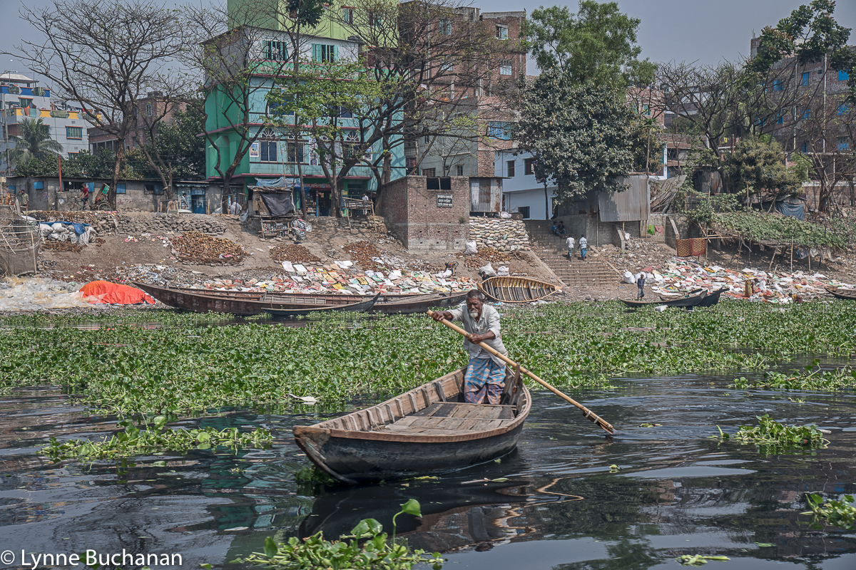 Buriganga Oarsman Rowing Past an Area with Discarded Plastic
