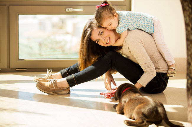 happy mom and daughter playing with dog
