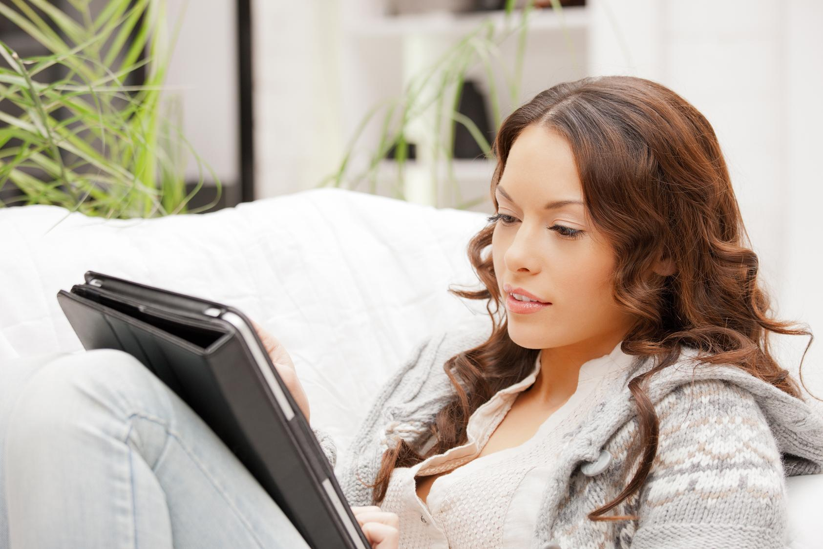 young woman reading from tablet computer