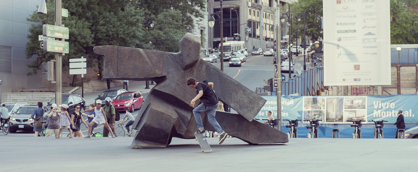 A teenager skateboards in front of  Taichi Single Whip  (1985) by Ju Ming, which is installed in Victoria Square, as a child imitates the sculpture's pose in the background, to the left. © Denise Caron