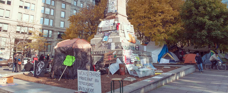 À l'automne2011, alors que le mouvement Occupons Montréal s'approprie le square Victoria, des pancartes sont installées sur le  Monument à la reine Victoria  (1869) de Marshall Wood. © Denise Caron