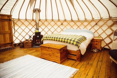 Inside the yurt is a super comfy king size bed with blankets with a roaring log fire