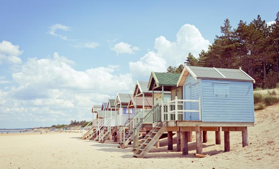 Wells-next-the-sea beachhuts along the beach in the sunshine