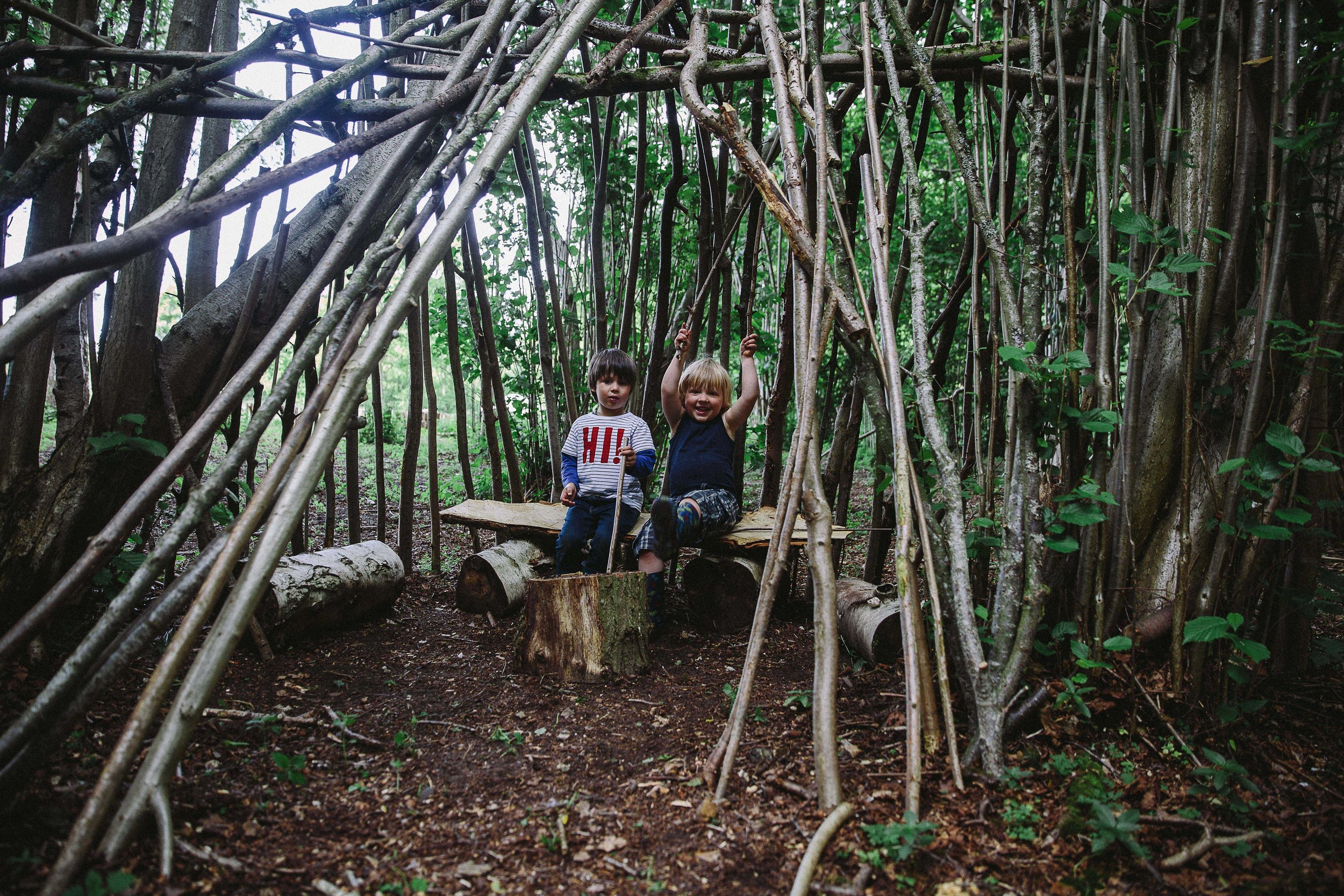 Boys playing in a den in the woods