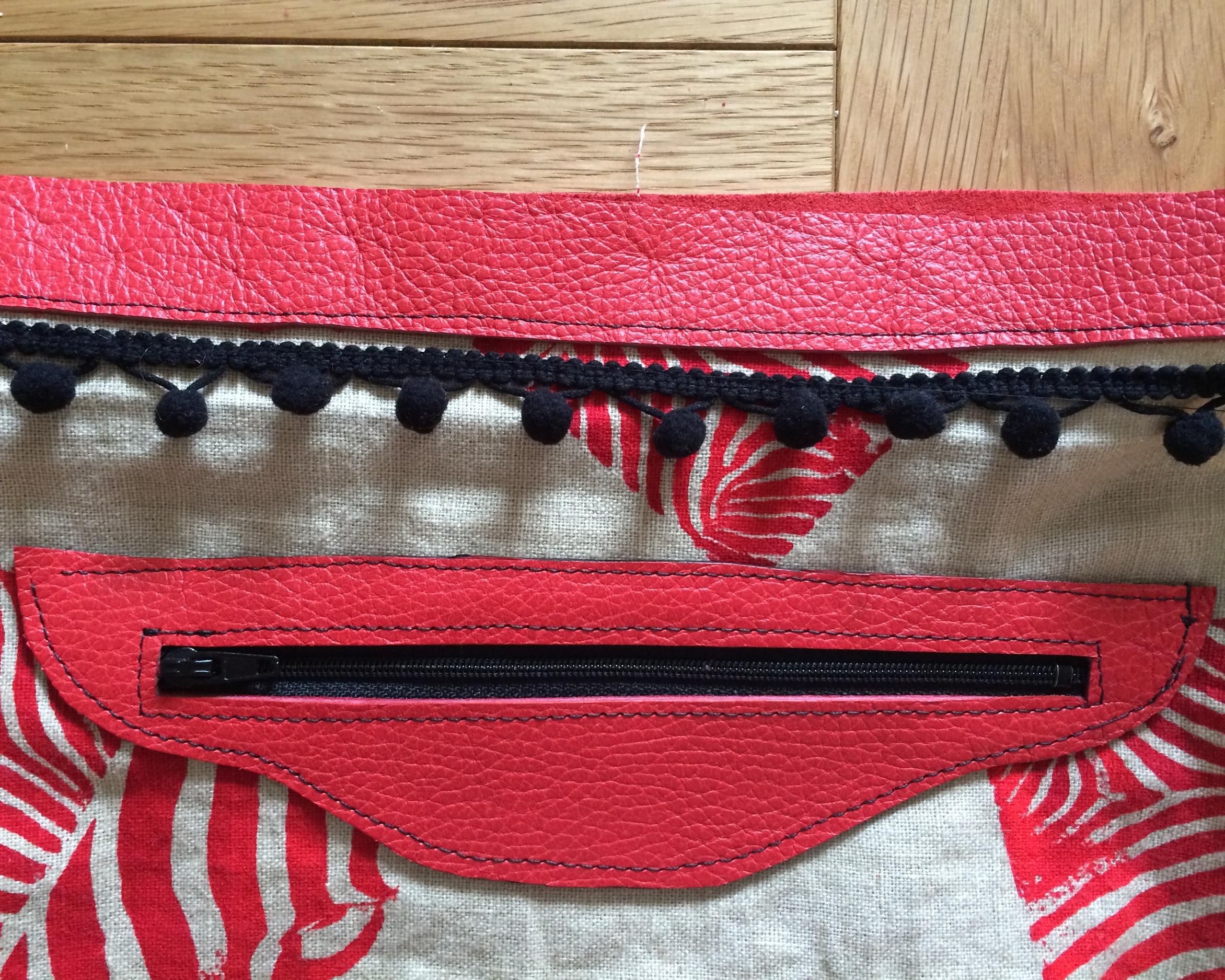 A close up of the pom pom trim and inside pocked detail