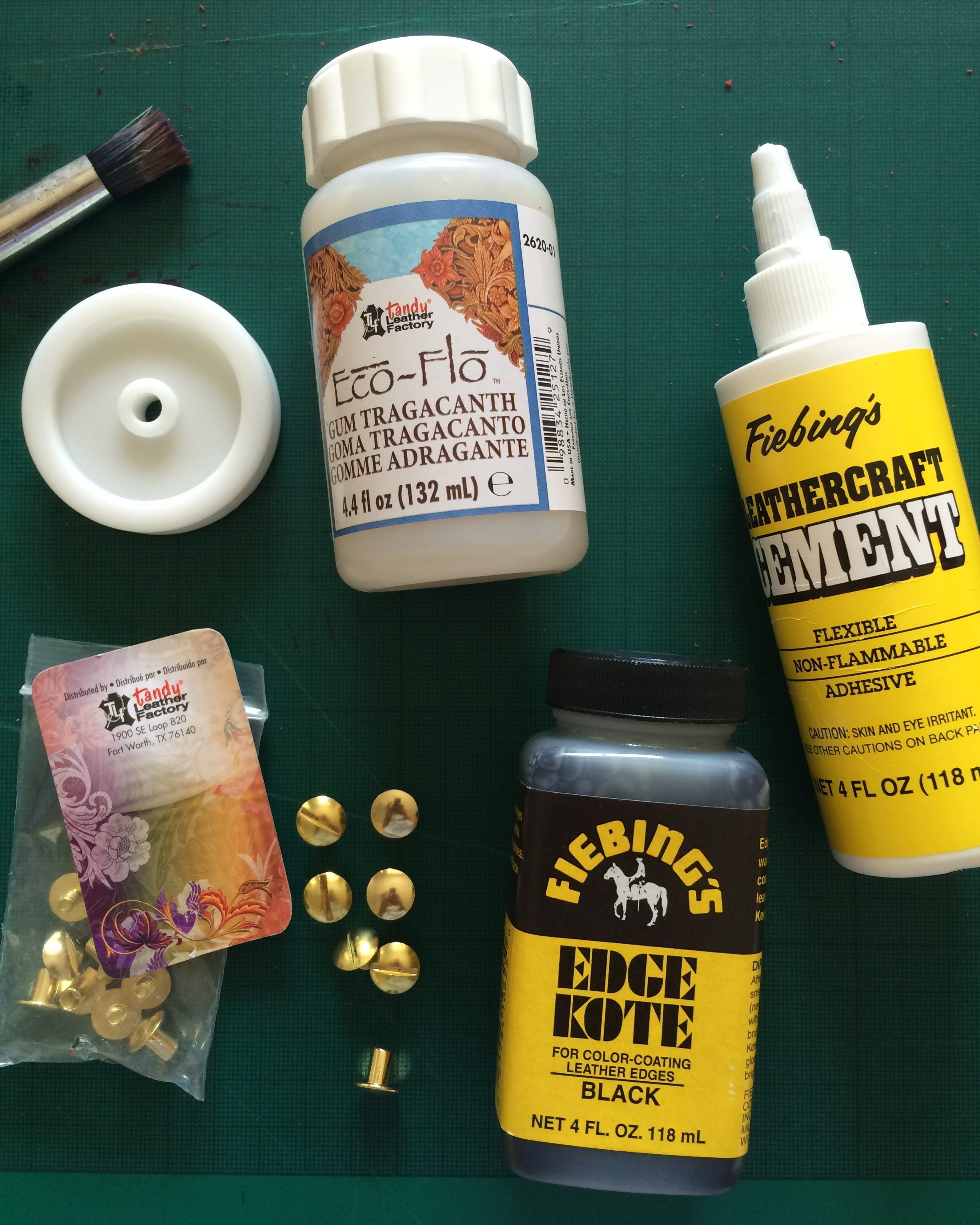Clockwise from left to right: the edge slicker; used in conjunction with the Gum Tragacanth to burnish and neaten the raw edges; Fiebing's leathercraft cement (i.e. leather glue!); Edge Kote to paint the raw edges; and finally the brass screw rivets (or Chicago screws as the website calls them).