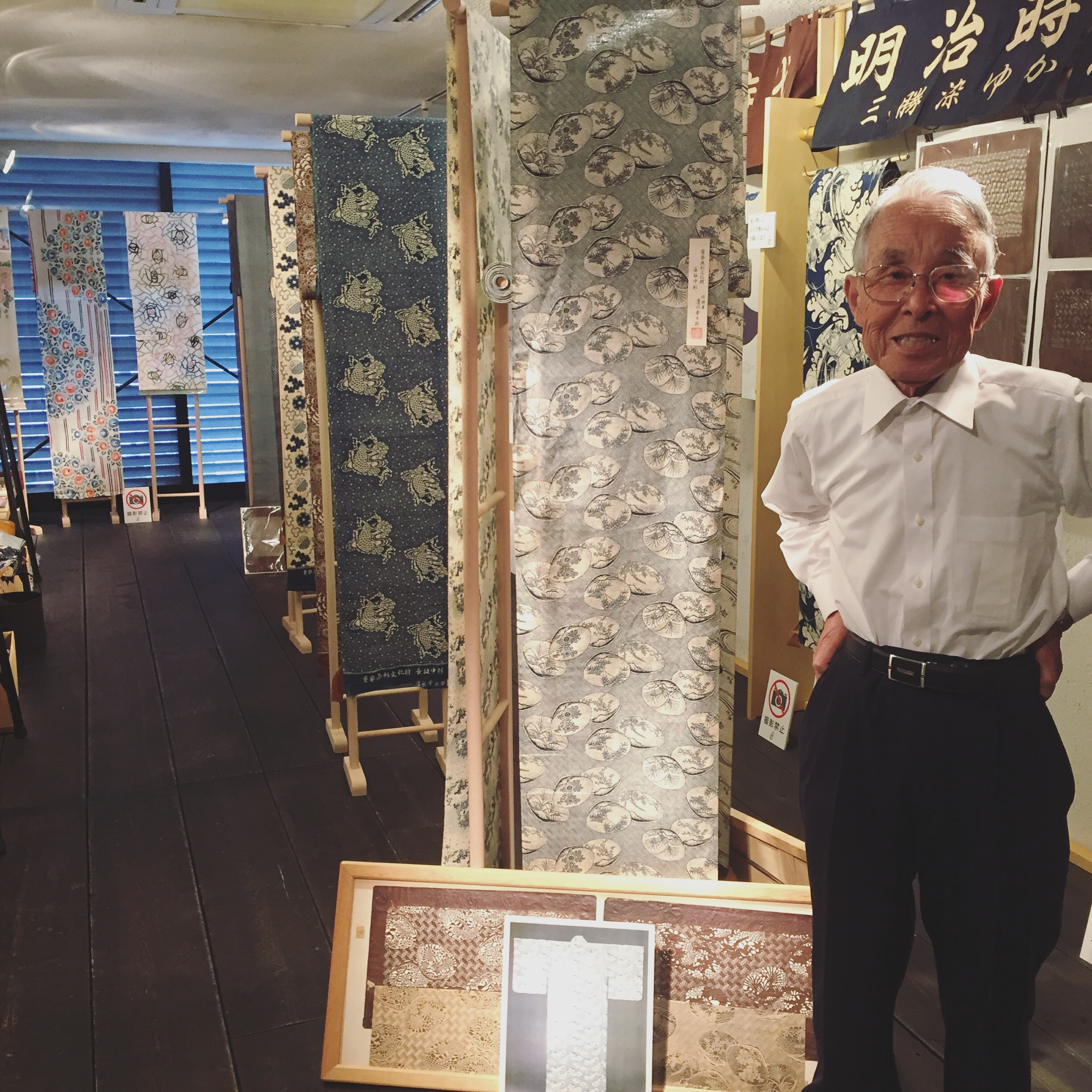 Mr. Shimizu next to his father's hand-dyed yukata textile at the Yukata Museum.