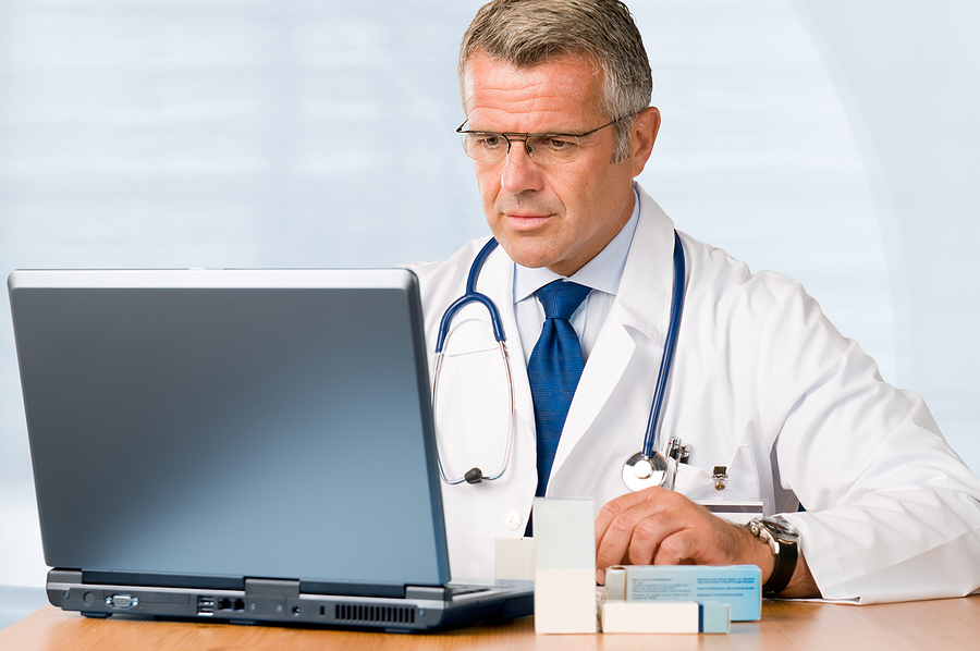 bigstock-Mature-doctor-working-on-lapto-14508200.jpg