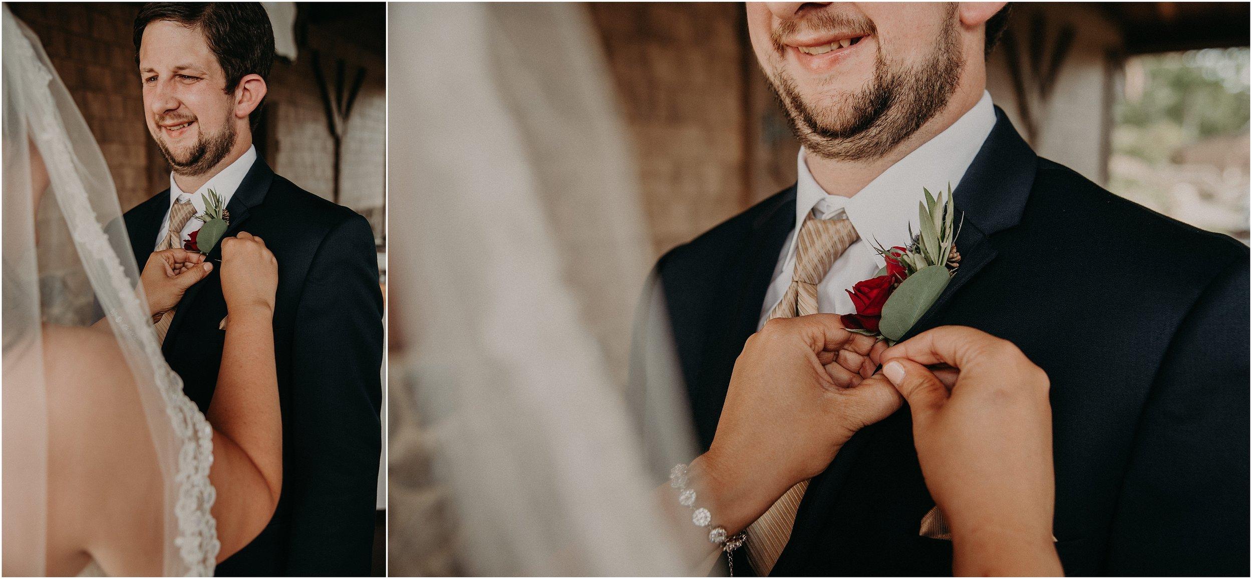 Bride pins groom's bouquet onto his suit lapel