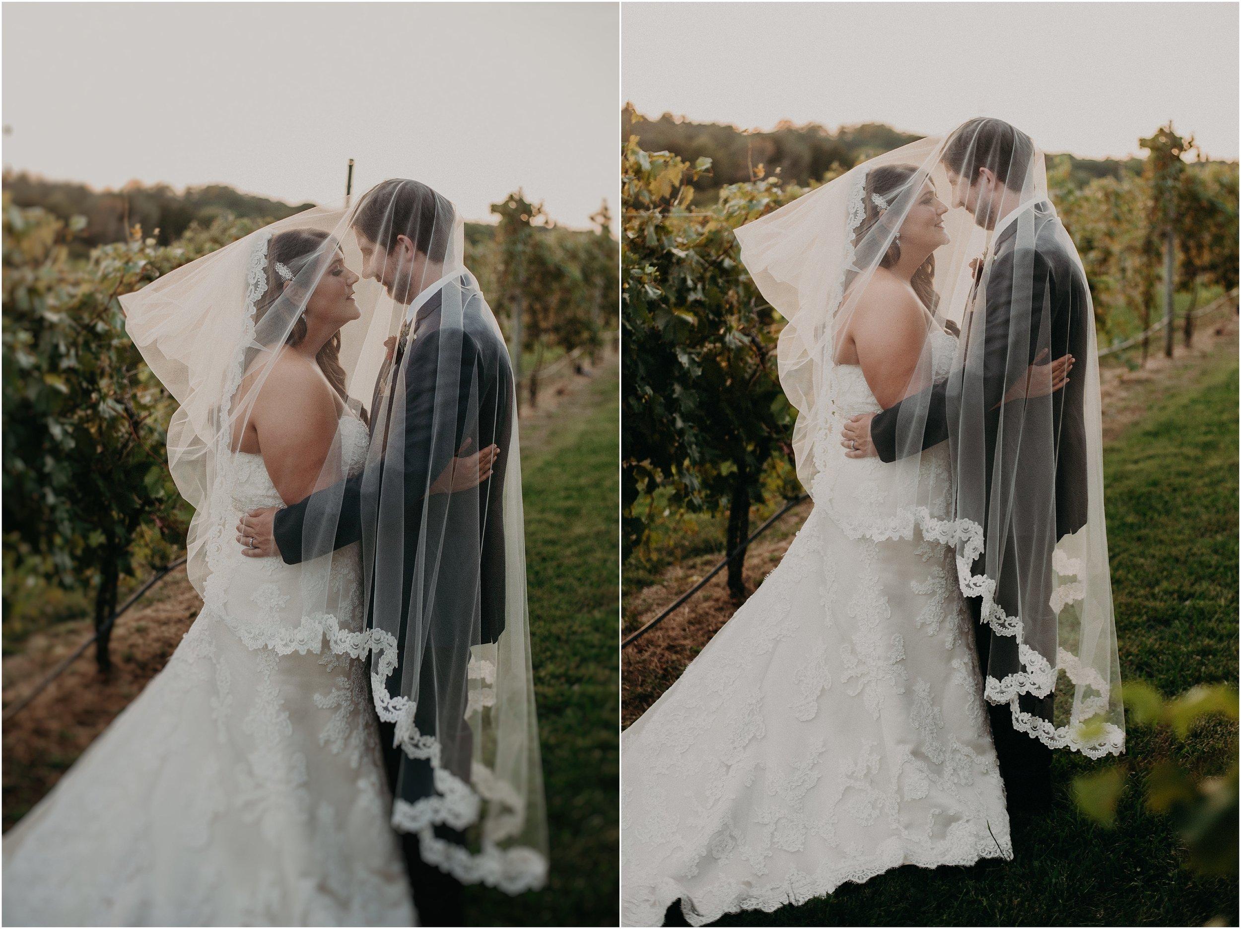 Wedding couple get cozy together beneath bride's cathedral veil