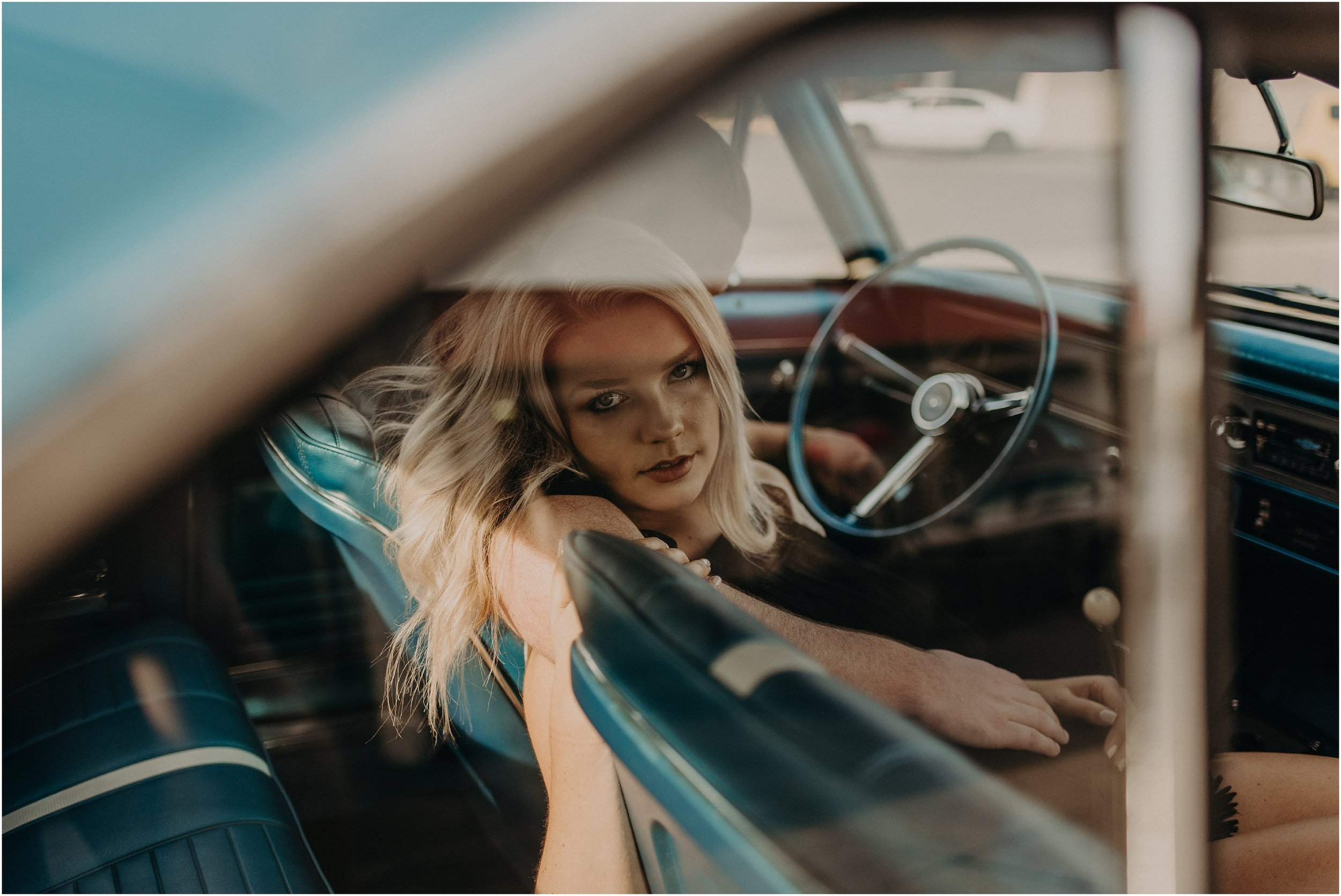 Blonde bombshell gives the camera a smoldering look during her engagement photos inside of a Chevy Nova SS