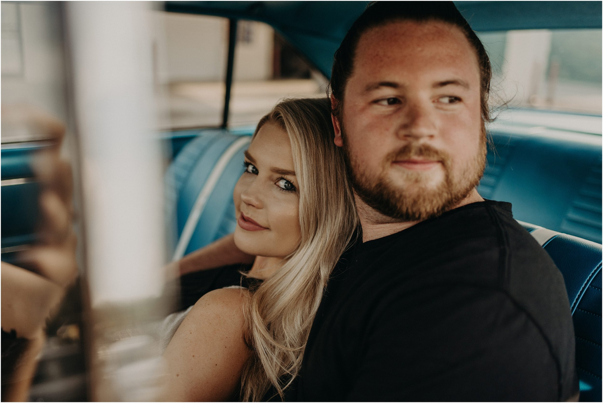 Cute couple snuggles for their car wash engagement photos