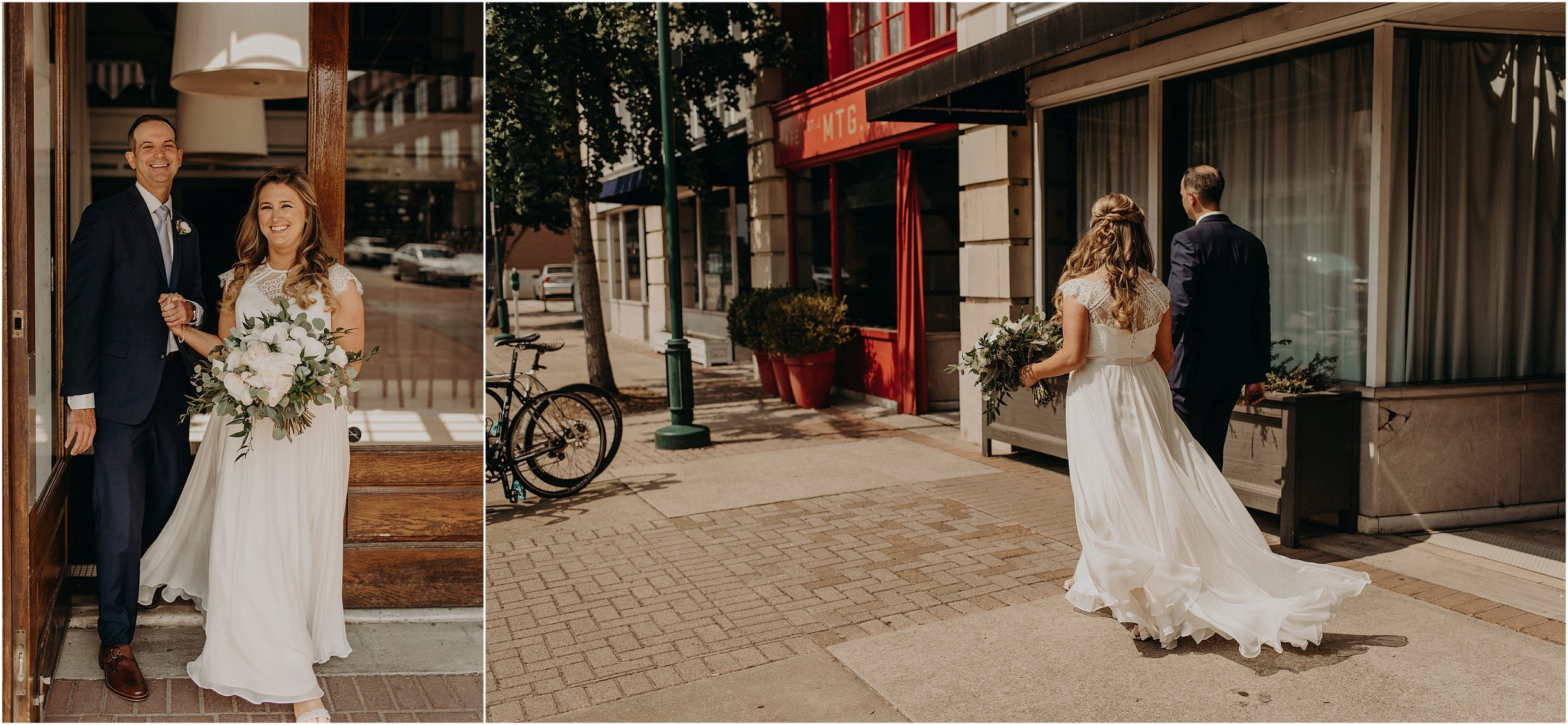 Bride and groom walk down the city sidewalk while her wedding gown blows in the breeze