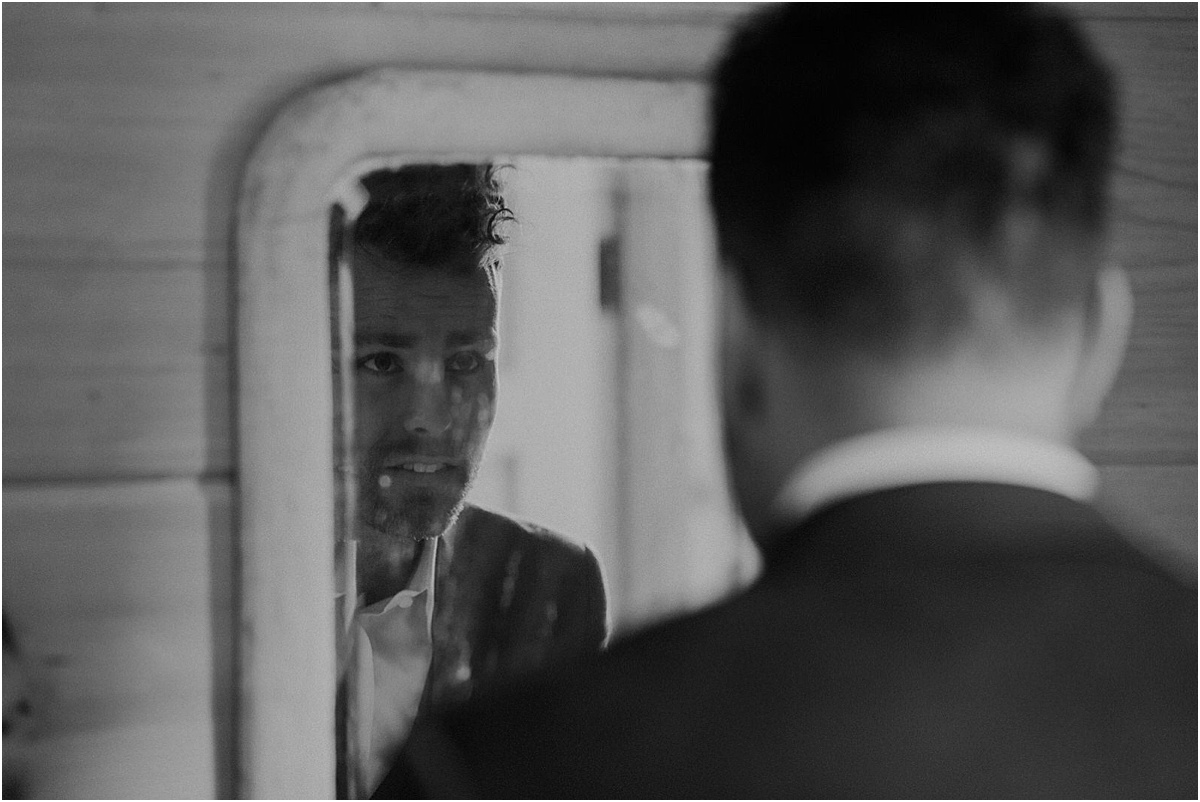 groom looking into mirror getting ready before wedding ceremony