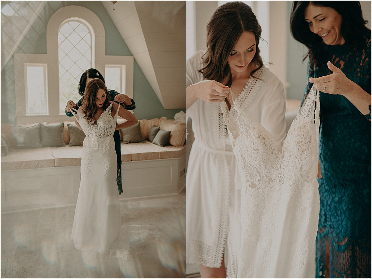 bride and mother putting on white wedding dress