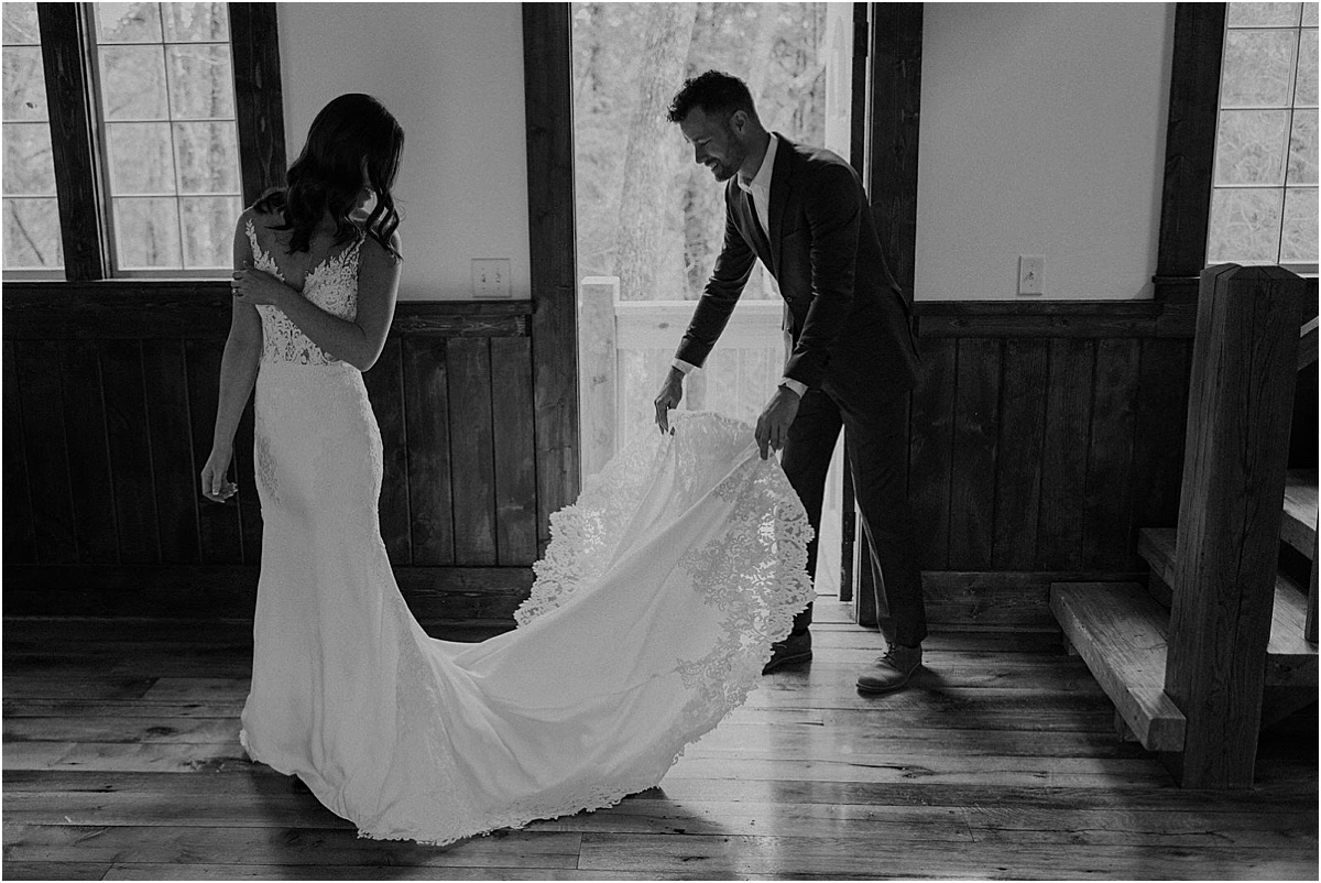 groom helping bride with her white wedding dress train