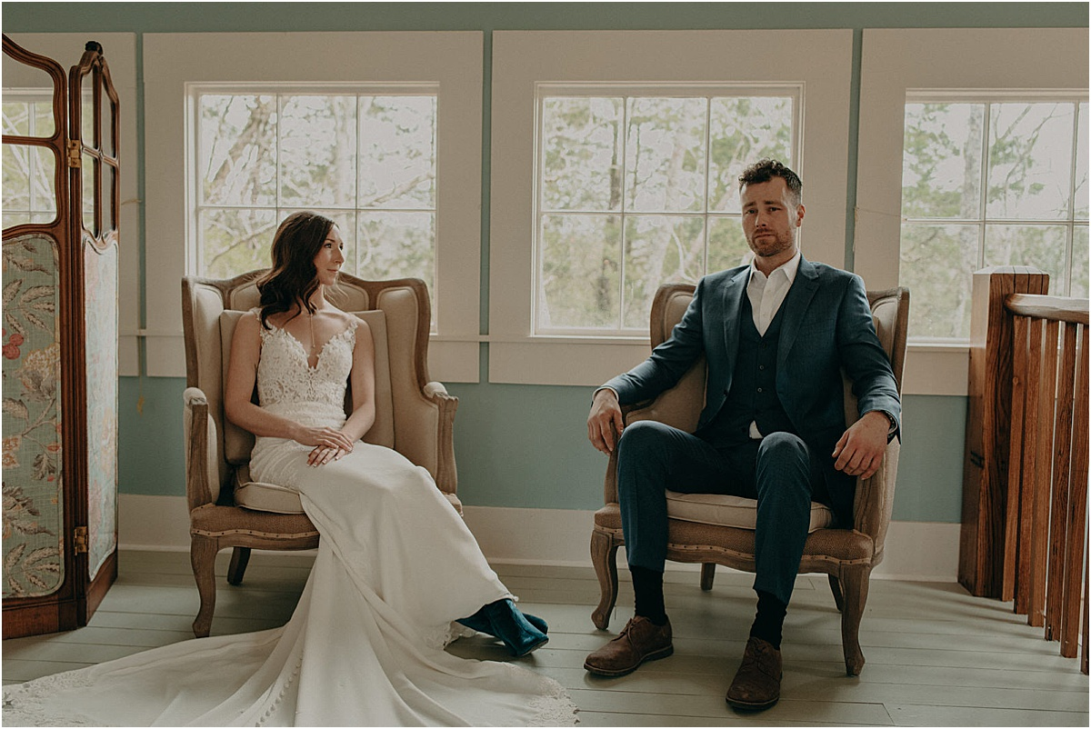 bride and groom sitting in antique chairs in blue room