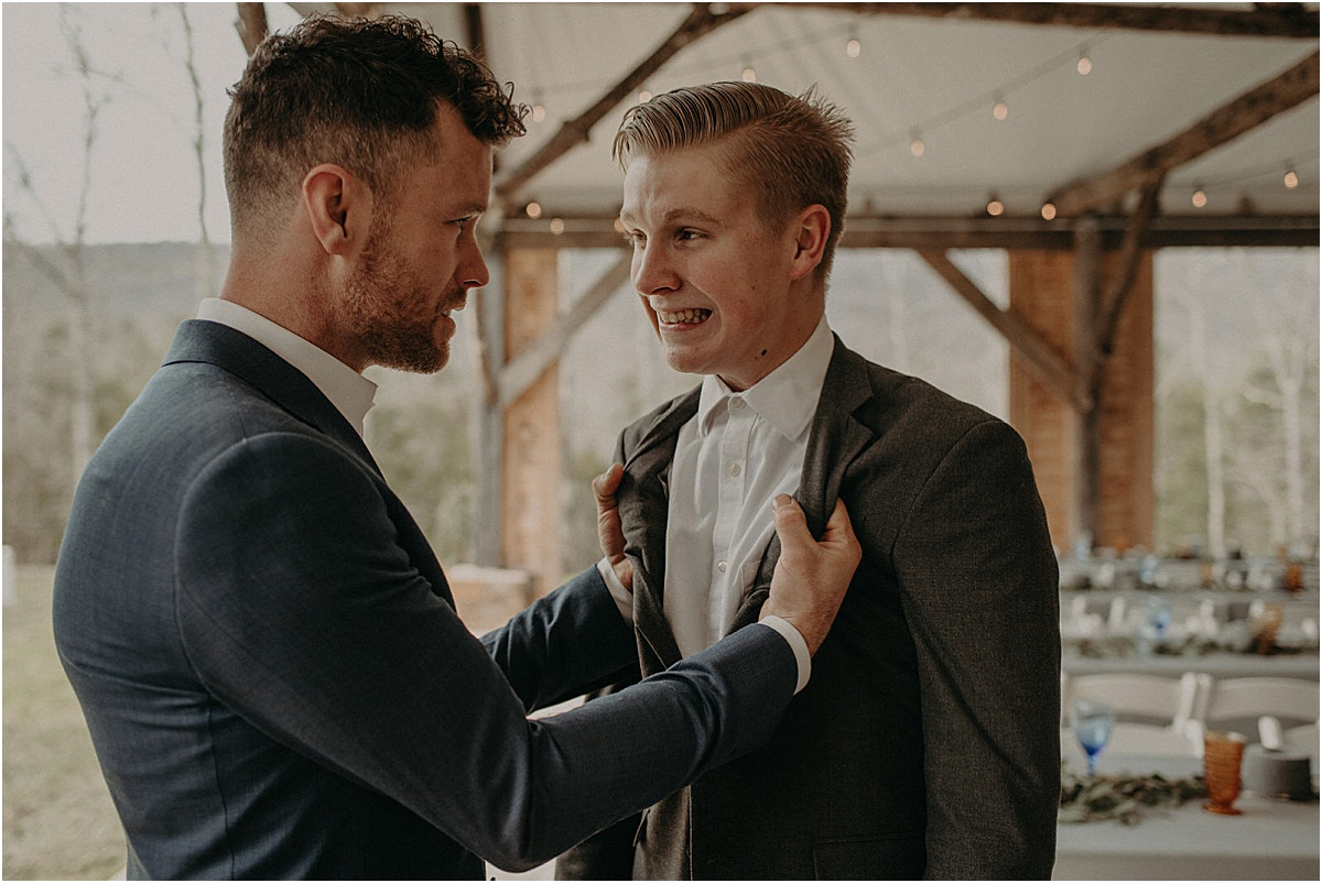 groom grabbing friends suit before wedding ceremony
