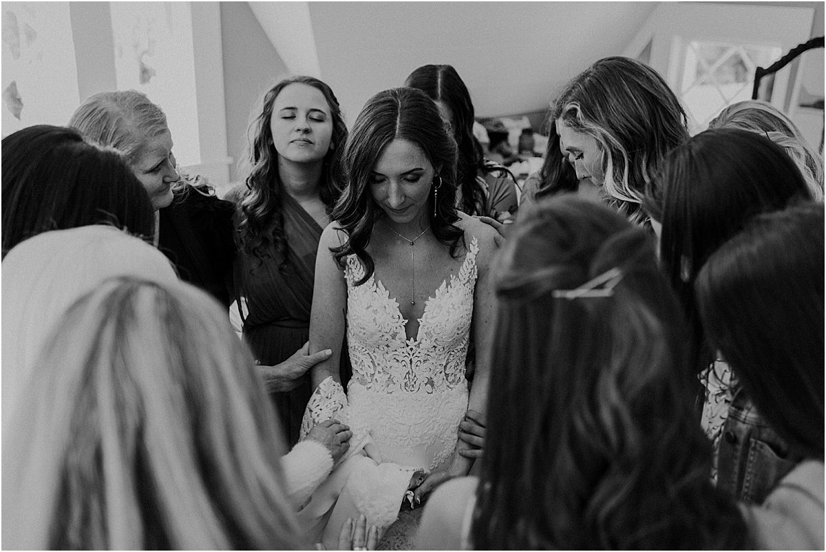 bridesmaids praying over bride before her wedding ceremony