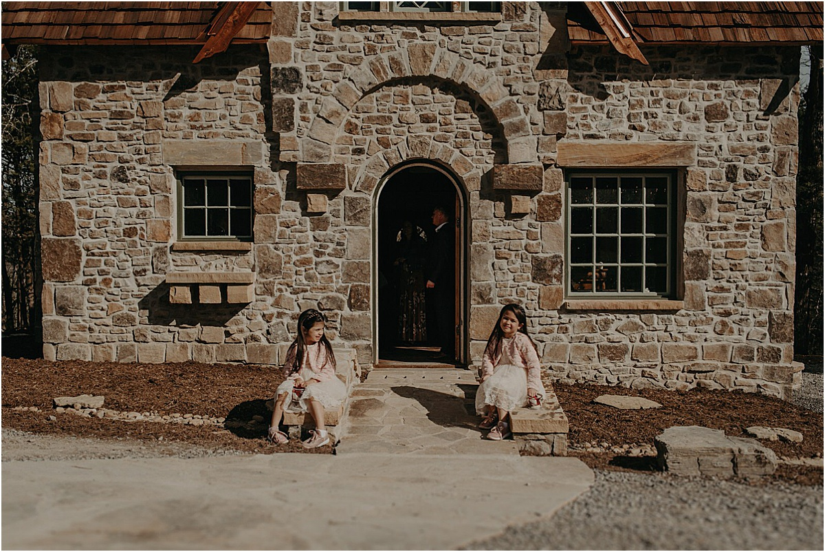 two girls sitting on the ground in front of brick cottage