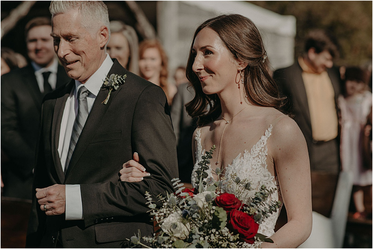 bride walking down the aisle during wedding ceremony with father