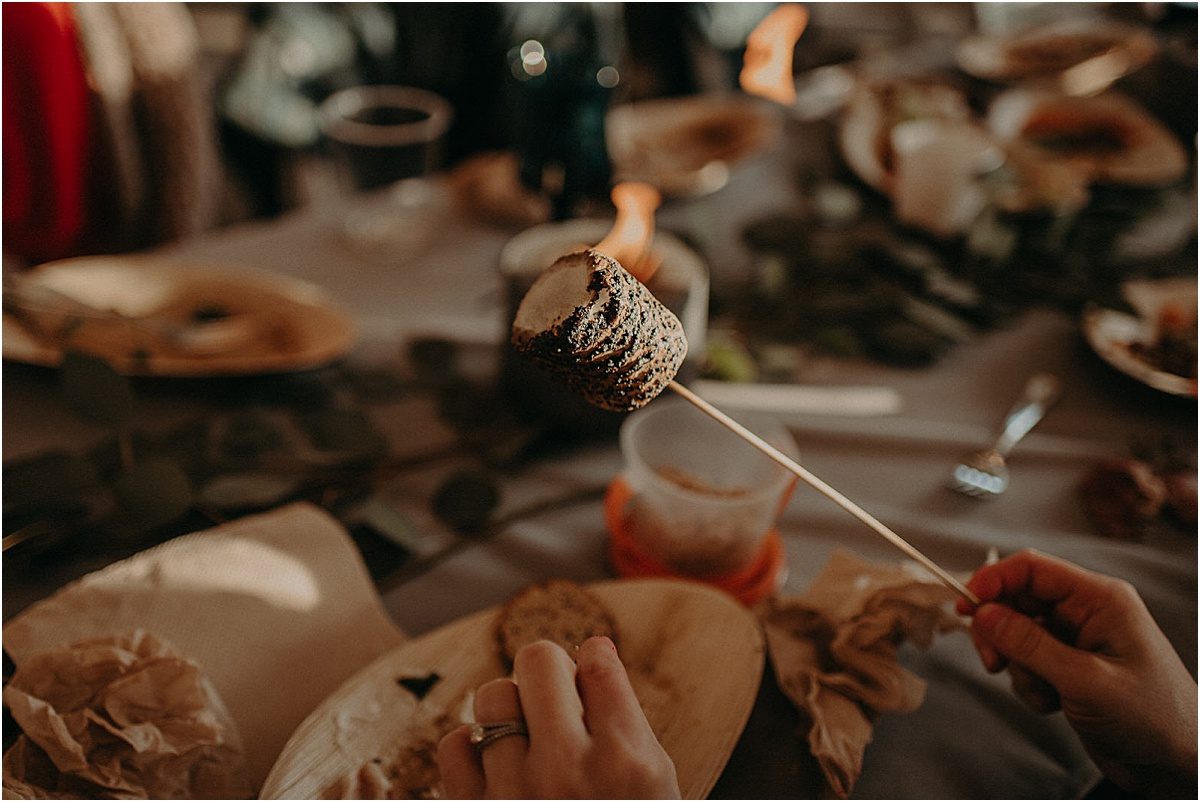 guest holding roasted marshmallow at wedding reception