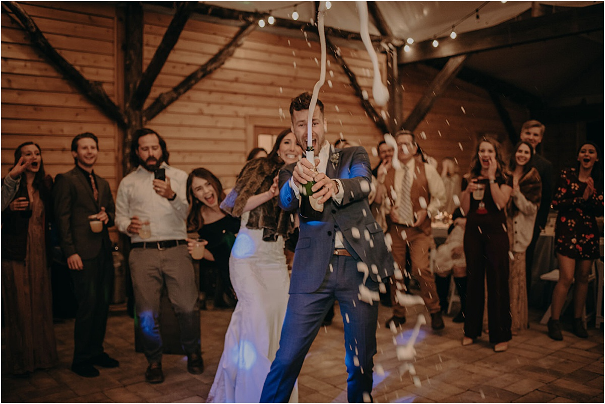 bride and groom popping champagne with guests at wedding reception