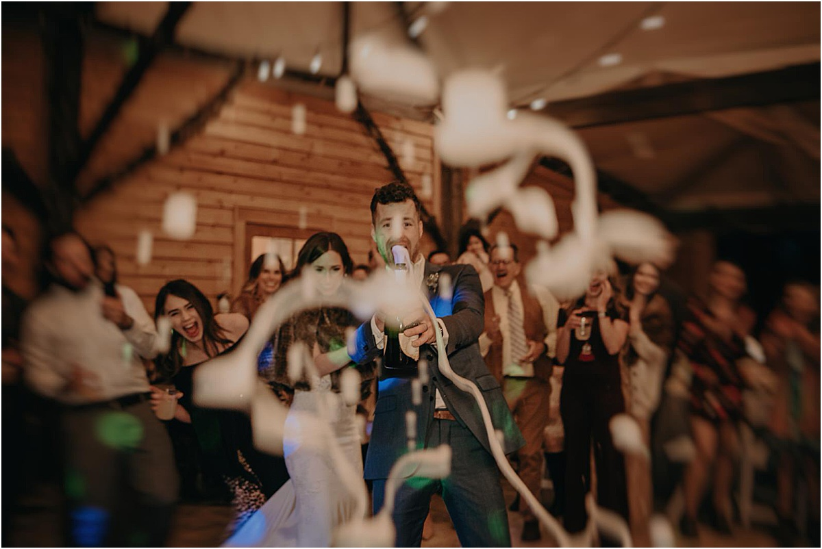 bride and groom popping champagne at camera during wedding reception