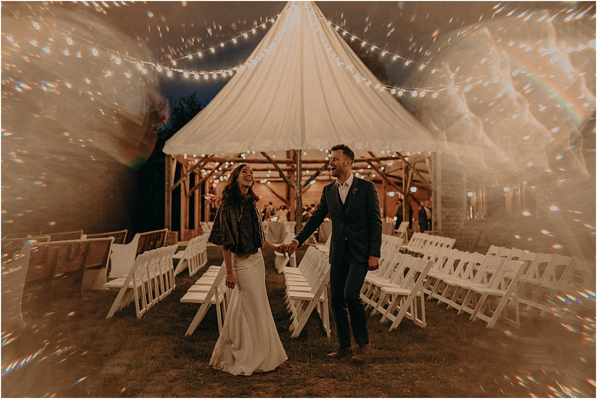 bride and groom smiling in front of wedding tent at night