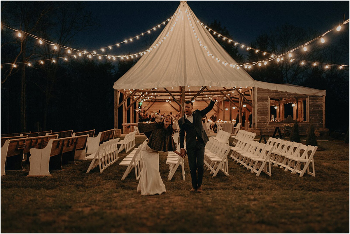 bride and groom celebrating in front of tent and lights at night
