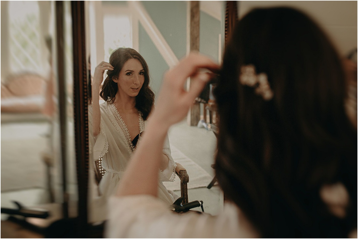 bride fixing her hair in front of mirror before wedding ceremony