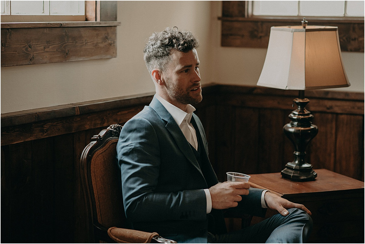groom in blue suit sitting down and drinking in a rustic room