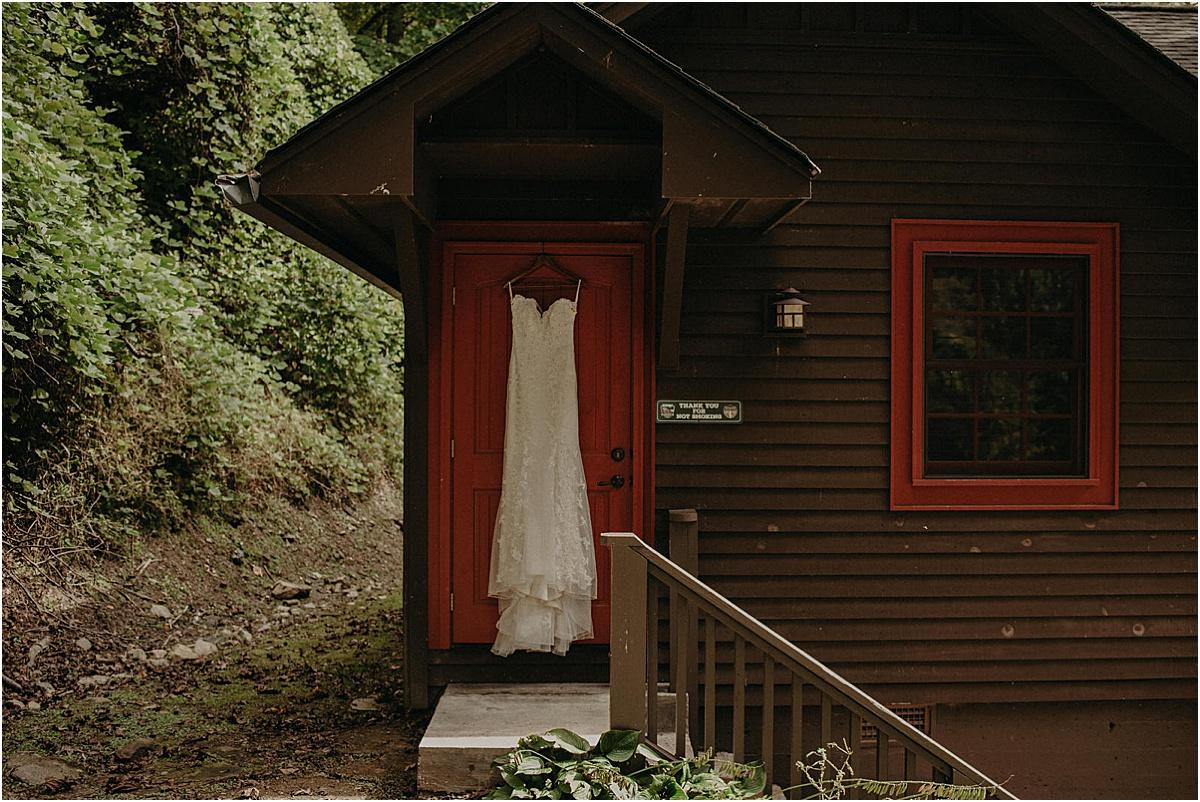 wedding dress hanging on red door of lodge