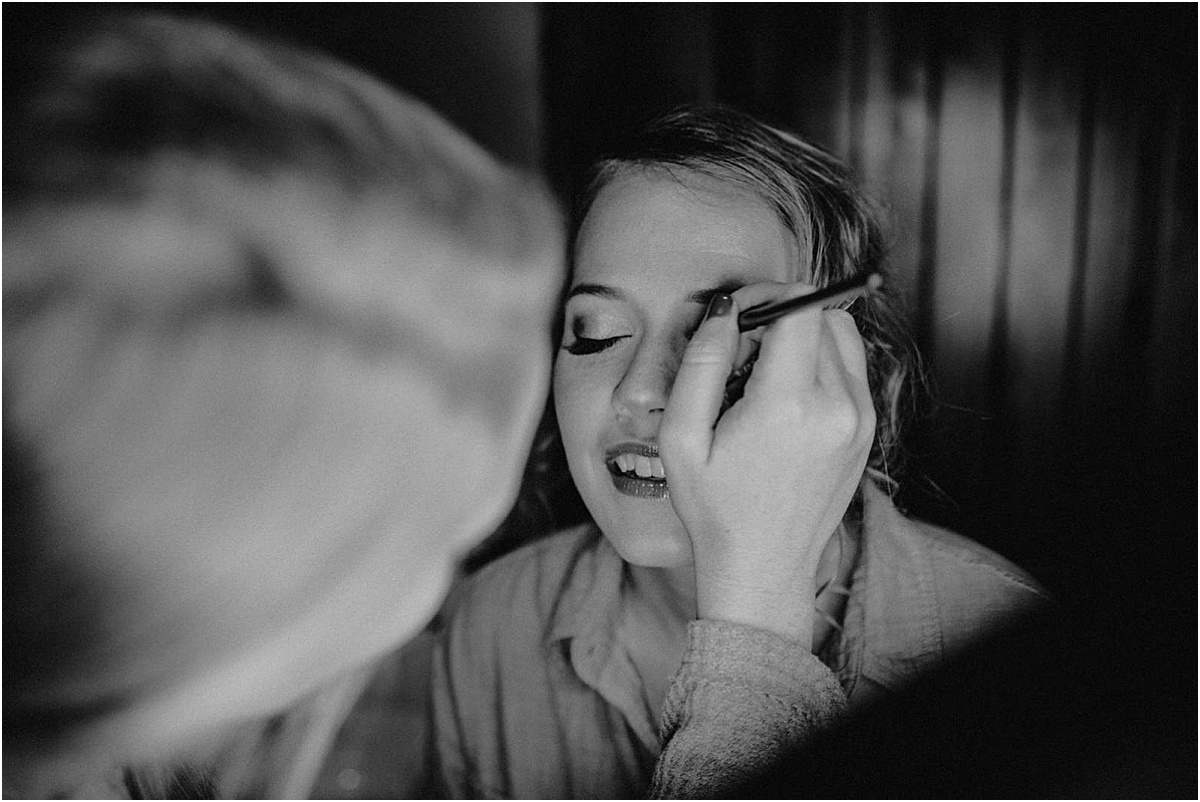 girl getting makeup done before wedding ceremony