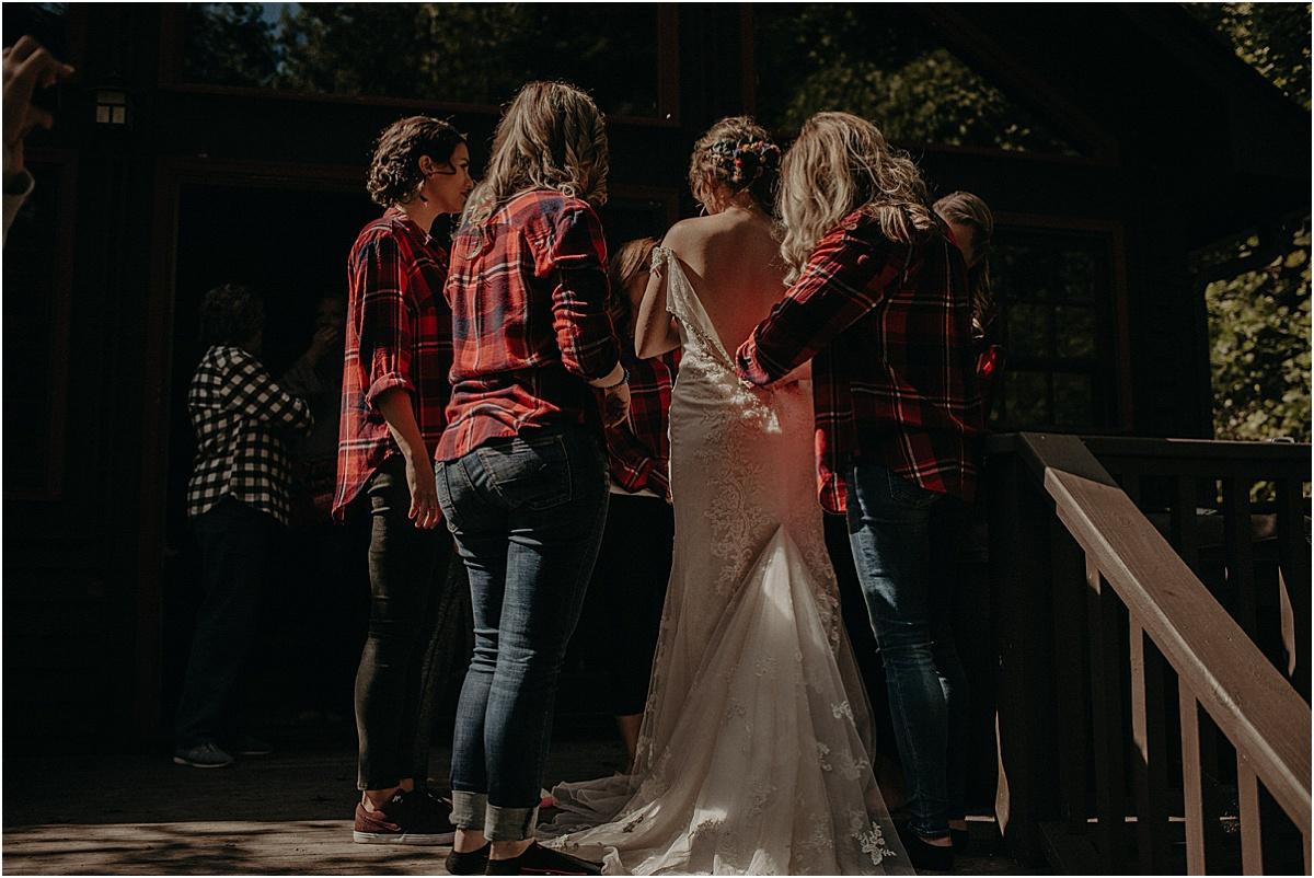 bridesmaids helping bride button wedding dress before ceremony
