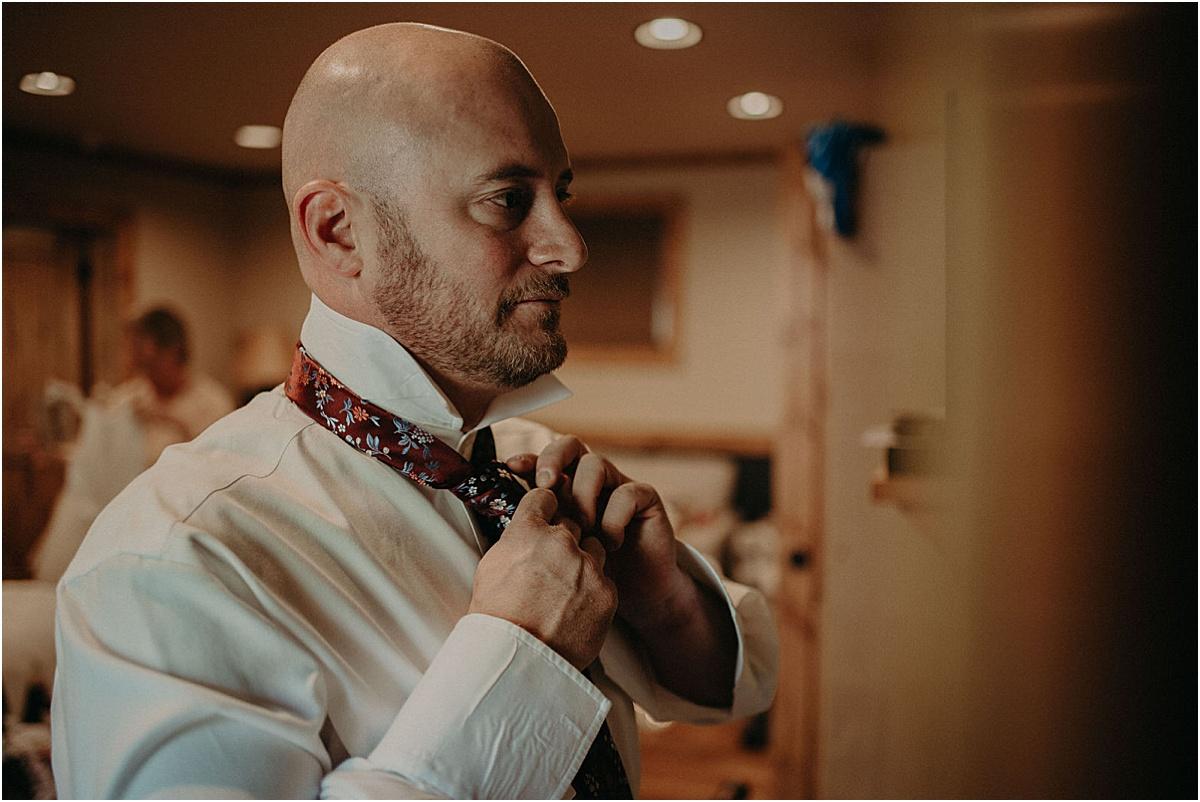 groom putting on tie before wedding ceremony