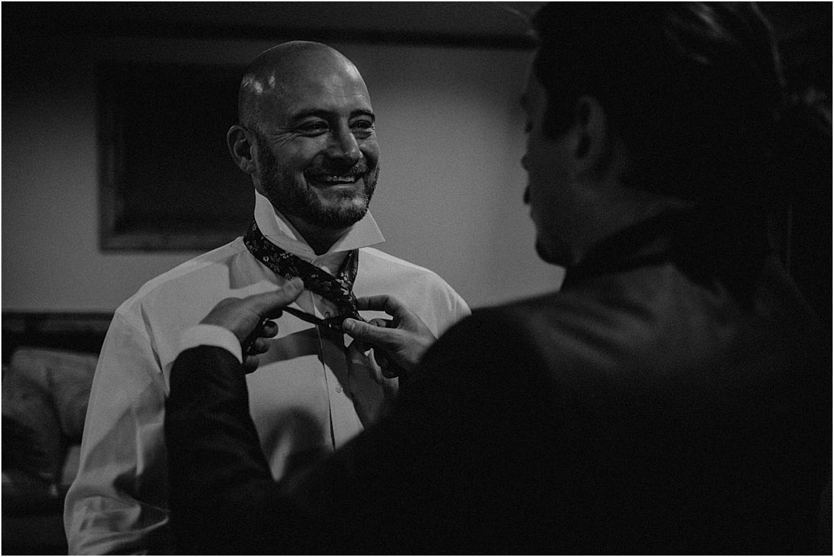 groomsmen helping groom put on tie