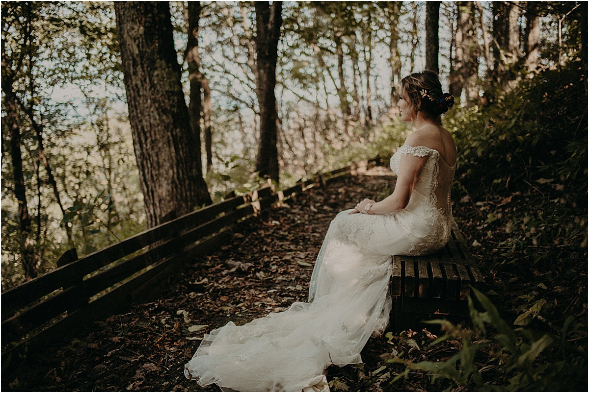 bride sitting on bench in woods before wedding ceremony