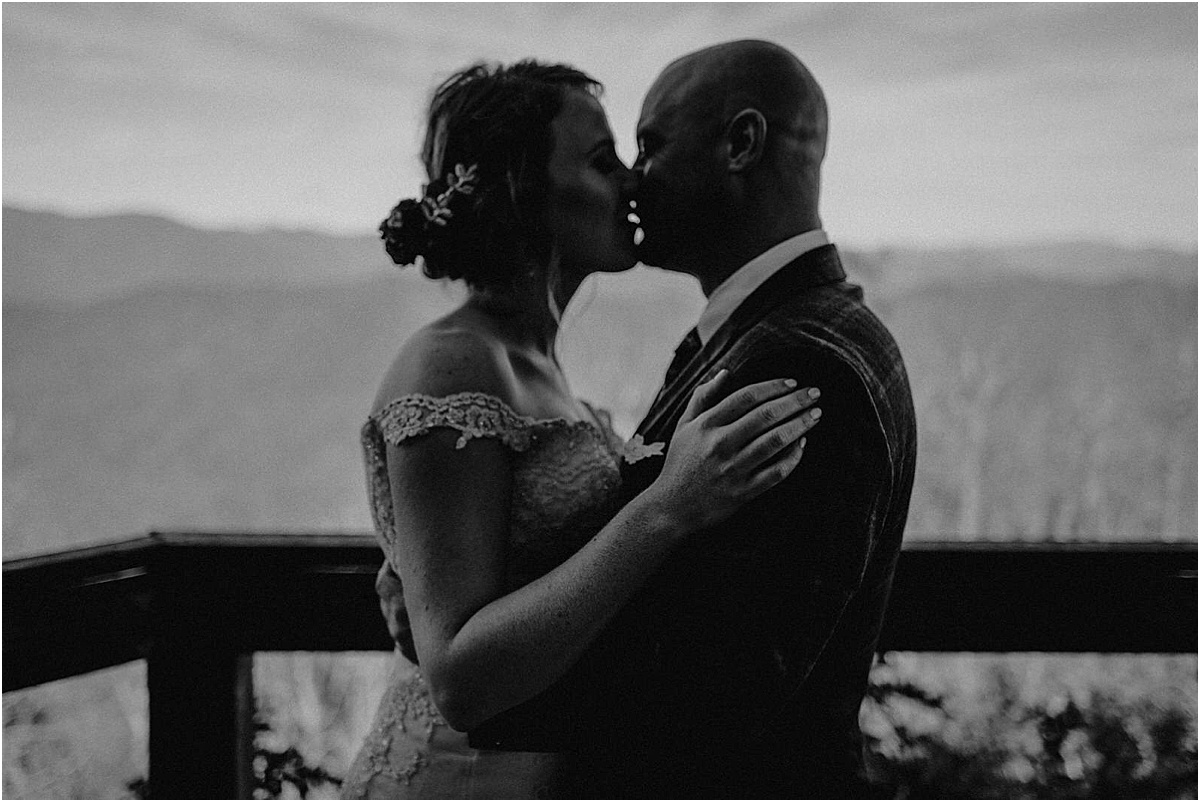 bride and groom kissing in front of north carolina hills