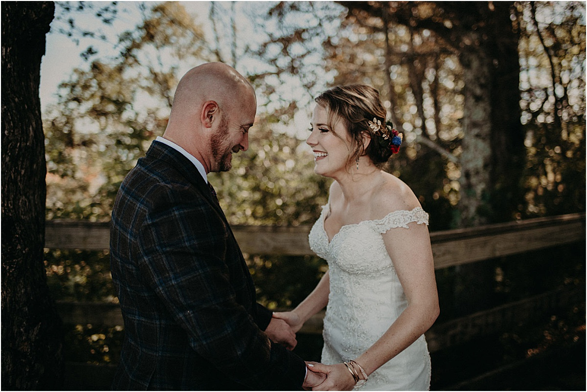 bride and groom smiling at each other during first look