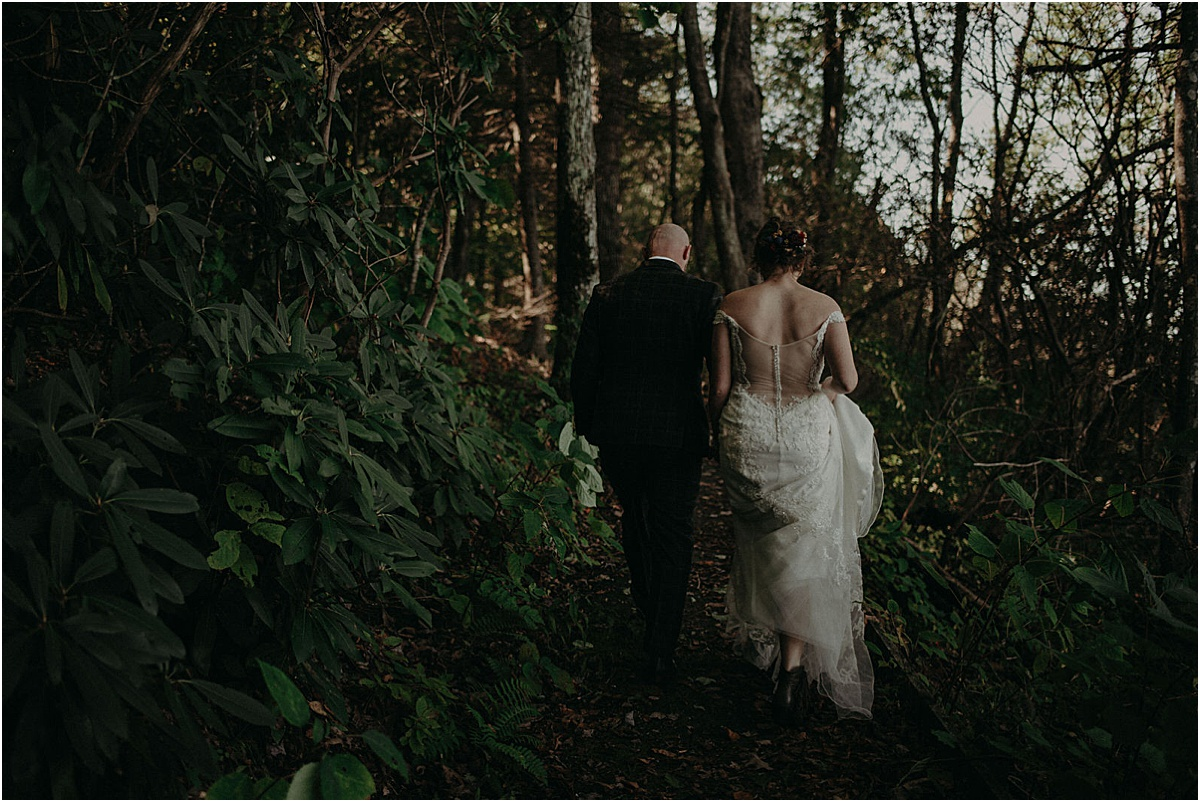 bride and groom walking through green forest in north carolina